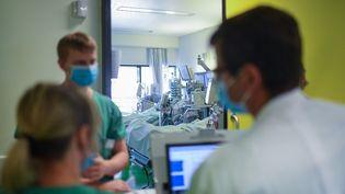 Des membres du personnel soignant de l'hôpital universitaire d'Aix-la-Chapelle (Allemagne) discutent devant la chambre d'un malade du Covid-19 en soins intensifs, le 15 avril 2020. (INA FASSBENDER / AFP)