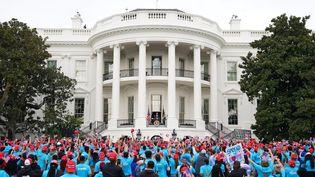 Le présisent américain Donald Trump fait une apparition depuis le balcon de la Maison Blanche, le 10 octobre 2020, devant plusieurs centaines de sympathisants rassemblés dans les jardins. (MANDEL NGAN / AFP)