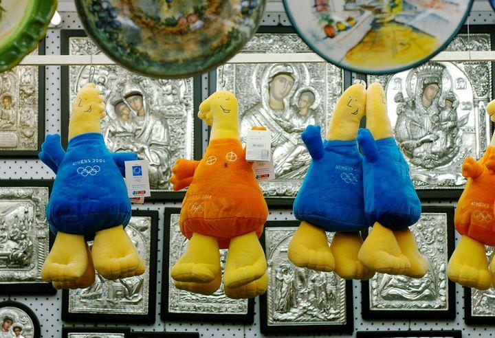 Phevos et Athéna, mascottes des JO d'Athènes, dans un magasin de souvenirs de la capitale grecque, le 5 août 2004. (OLIVER MULTHAUP / DPA)