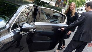 Un chauffeur de VTC ouvre la porte à une cliente, à Paris, le 24 avril 2014. (PIERRE ANDRIEU / AFP)