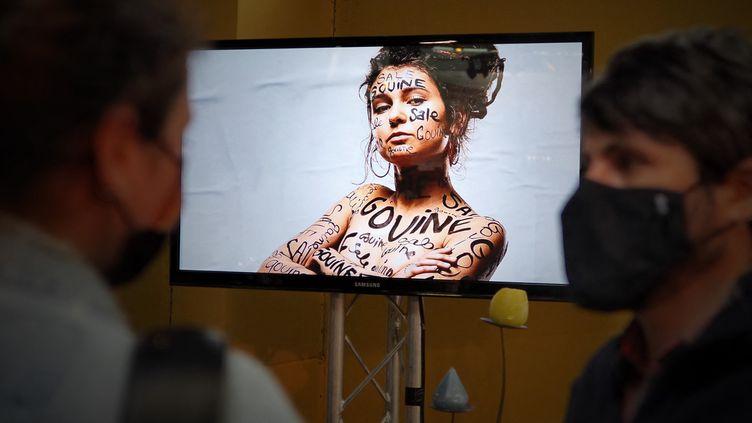 """Des festivaliers devant un écran diffusant la campagne de préventions des violences """"Ici c'est cool"""" au Printemps de Bourges, le 23 juin 2021. (GUILLAUME SOUVANT / AFP)"""