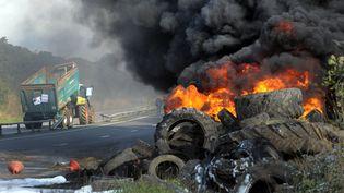 Des agriculteurs bretons brûlent des pneus près de la route, le 14 octobre, lors d'une manifestation à Morlaix (Finistère) en compagnie de salariés de différentes entreprises agroalimentaires. (FRED TANNEAU / AFP)