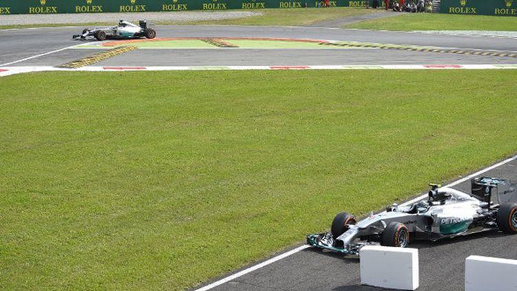 Lewis Hamilton profite du freinage raté de Nico Rosberg pour prendre la tête du GP d'Italie à Monza (OLIVIER MORIN / AFP)