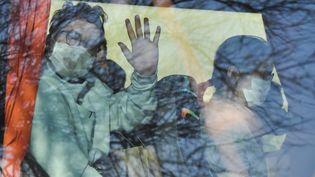 Un des Français rapatriés salue de l'autocar qui les transfère au centre de vacances de Carry-le-Rouet où ils vont être confinés pendant 14 jours, le 31 janvier 2020. (GERARD JULIEN / AFP)