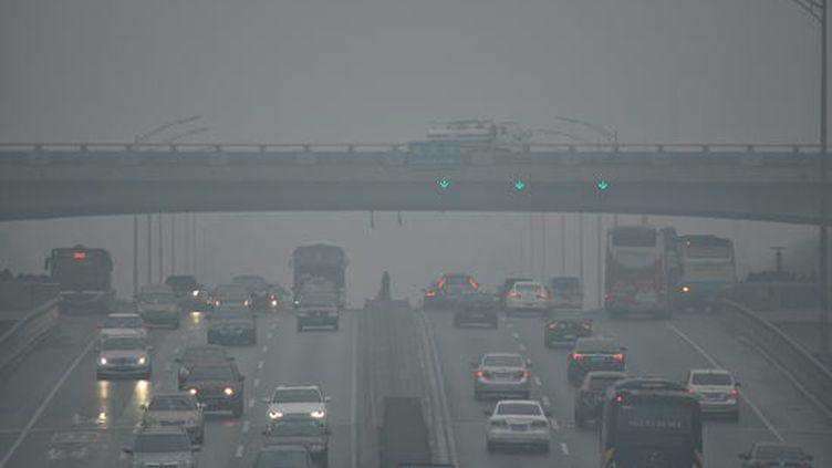 Des véhicules circulent dans un brouillard à Pékin (Chine), le 14 décembre 2015. (IMAGINECHINA / AFP)
