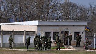 Des militaires russes devant une base militaire ukrainienne de Smféropol, en Crimée, samedi 8 mars 2014. (ELENA SAMOYLENKO / ANADOLU AGENCY / AFP)