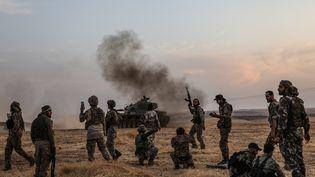 Des soldats turcs et des combattants syriens soutenus par la Turquie rassemblés dans la banlieue nord de la ville syrienne de Manbij, près de la frontière turque, le 14 octobre 2019. (ZEIN AL RIFAI / AFP)