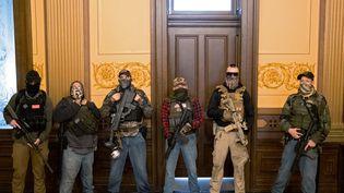 Des manifestants armés dénoncent les mesures de confinement, le 30 avril 2020, à l'intérieur du Capitole du Michigan, aux Etats-Unis. (SETH HERALD / REUTERS)