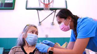 Une infirmière s'apprêtant à injecter une dose de vaccin contre le Covid-19 à une femme, en Californie, aux Etats-Unis, le 29 juillet 2021. (MARIO TAMA / GETTY IMAGES NORTH AMERICA / AFP)