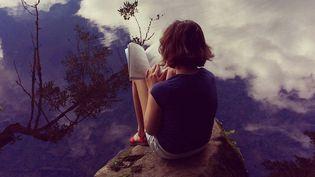 Enfant lisant au bord d'un lac  (Cyndi Monaghan / Getty)