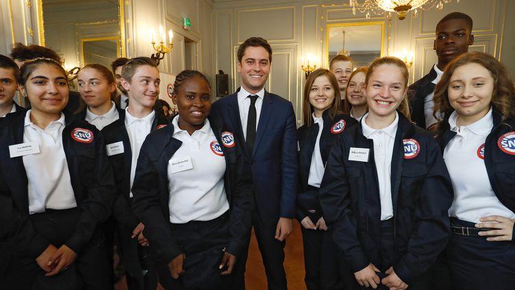 Gabriel Attal (avec la cravate au centre) et des jeunes portant l'uniforme du Service national universel, le 18 avril 2019, à Paris. (FRANCOIS GUILLOT / AFP)