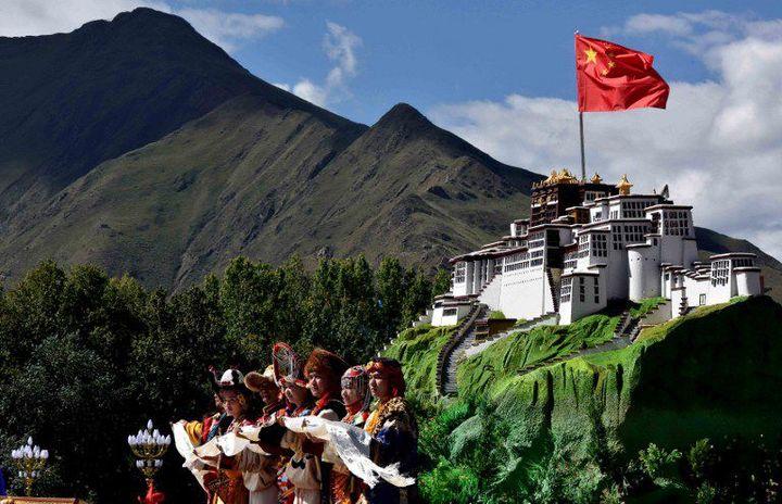 Des Tibétains habillés de façon traditionnelle posent devant une représentation du Potala le 8 septembre 2015, à l'occasion du 50e anniversaire de la fondation de la Région autonome. Le Potala est l'ancien palais du dalaï-lama. (LI TAO / XINHUA)