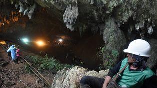 Un homme observe les opérations de secours pour retrouver 13 personnes disparues dans la grotte de Tham Luang en Thaïlande, le 27 juin 2018. (LILLIAN SUWANRUMPHA / AFP)