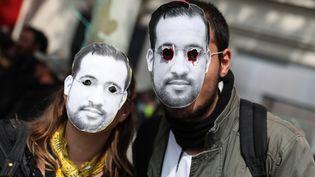 """Des manifestants portent des masques d'Alexandre Benalla à Paris, le 1er mai 2019. C'est le 1er mai 2018 que l'ancien chargé de mission élyséen avait pris part à une interpellation musclée qui avait déclenchée la tentaculaire """"affaire Benalla"""". (KENZO TRIBOUILLARD / AFP)"""