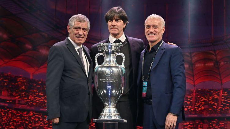 Fernando Santos, l'entraîneur du Portugal, Joachim Loew, le coach allemand et Didier Deschamps, l'entraîneur des Bleus, avec le trophée de l'Euro 2020, le 30 novembre 2019 à Bucarest (Roumanie). (FABRICE COFFRINI / AFP)