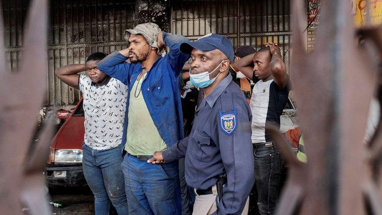 Johannesburg, le 27 mars 2020 : un policier sud-africain arrête des personnes en possession d'alcool, interdit de consommation par les autorités depuis la mise en place du confinement pour lutter contre l'épidémie de coronavirus. (Luca Sola / AFP)