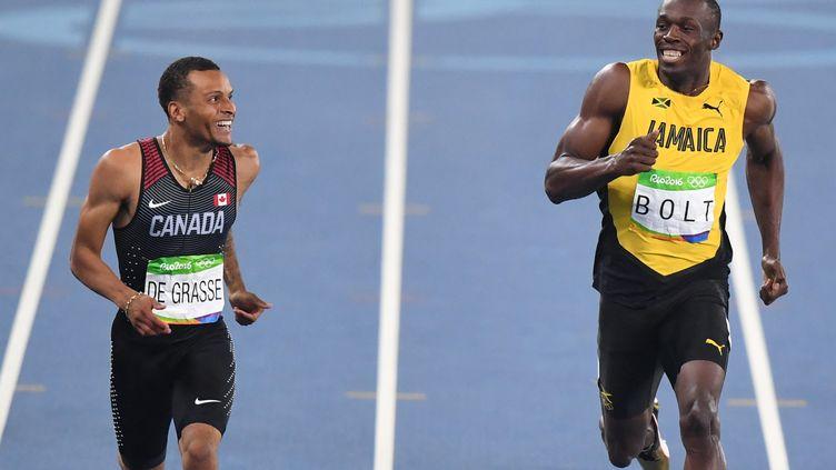Andre De Grasse et Usain Bolt à l'arrivée de la deuxième demi-finale  (PEDRO UGARTE / AFP)