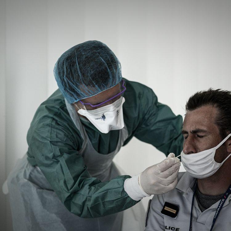 Un officier de policeeffectue un test PCR au coronavirus à l'aide d'un écouvilloninséré dans son nez à l'aéroport international de Bordeaux-Mérignac (Gironde) le 23 juillet 2020. (PHILIPPE LOPEZ / AFP)