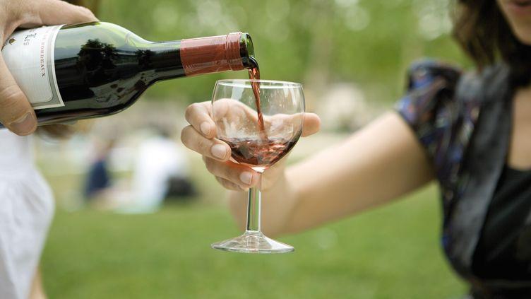 Une bouteille de vin est versée dans un verre lors d'un pique-nique. (MAXPPP)