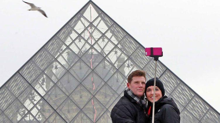 Des touristes se prennent en photo devant la pyramide du Louvre  (Rémy de la Mauvinière / AP / SIPA)