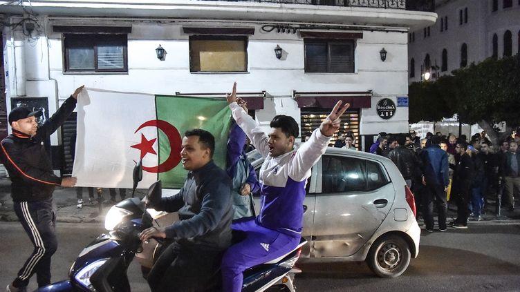Des Algériens laissent éclater leur joie, après que leprésident Abdelaziz Bouteflika a annoncé ne pas briguer un cinquième mandat, le 11 mars 2019. (RYAD KRAMDI / AFP)