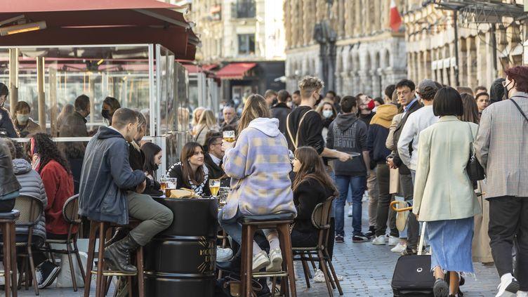 Des clients à une terrasse d'un bar, le 19 mai 2021. (SEBASTIEN COURDJI / XINHUA)