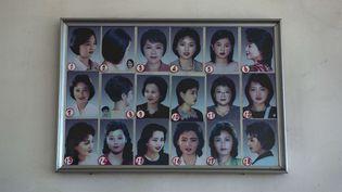 Photo prise au téléphone portable chez un coiffeur dePyongyang (Corée du Nord) présentant des modèles de coupes de cheveux. (DAVID GUTTENFELDER / AP / SIPA)