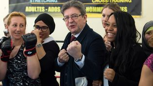 """Le candidat de """"La France insoumise"""", Jean-Luc Mélenchon, pose avec sa porte-parole SarahSoilihi à Marseille dans un club de boxeuses, le 8 mars 2017. (BERTRAND LANGLOIS / AFP)"""