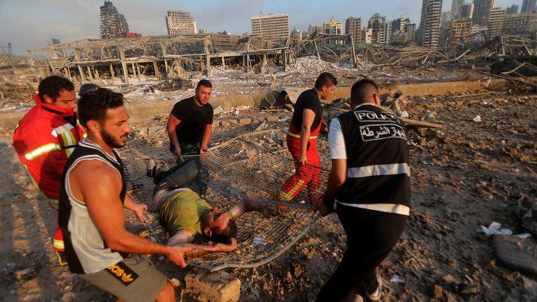Lessecoursévacuent un blessé, le 4 août 2020 à Beyrouth (Liban). (ANWAR AMRO / AFP)