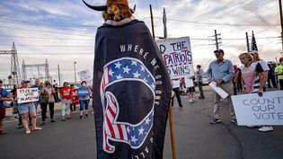"""Le militant QAnon Jake A., surnommé """"le loup de Yellowstone"""", manifeste aux côtés de militants pro-Trump devant le centre où a lieu le dépouillement de la présidentielle américaine, le 5 novembre 2020 à Phoenix, dans l'Arizona. (OLIVIER  TOURON / AFP)"""