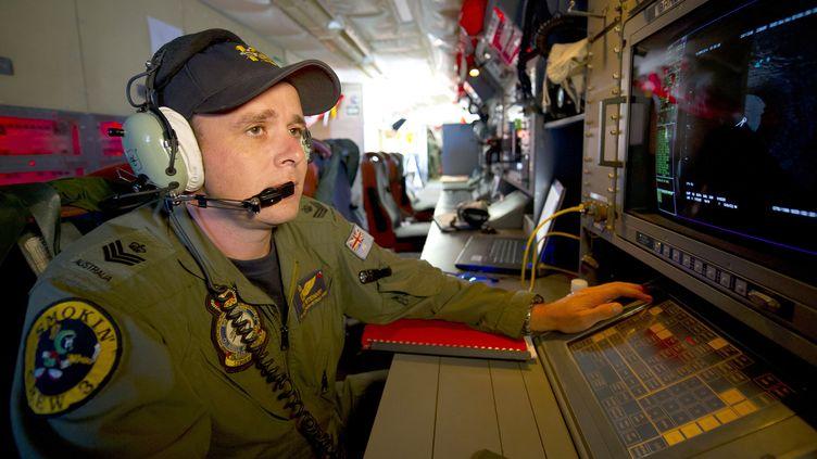 Un analyste de l'armée de l'air australienne surveillant un radar à bord d'un avion Orion, à la recherche des débris du vol MH370, le 19 mars 2014 dans l'océan Indien. (HAMISH PATERSON / AUSTRALIAN DEFENCE)