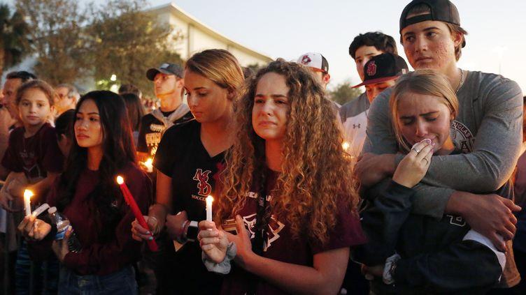Des jeunes Floridiens assistent, à Parkland (Floride, Etats-Unis) à un hommage, le 15 février 2018, aux victimes de la tuerie perpétrée dans un lycée de la ville, qui a fait 17 morts. (RHONA WISE / AFP)