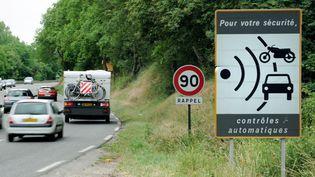 Des voitures passent devant un panneau annonçant la proximité d'un radar, le 2 juin 2011 près de Vienne (Rhône). (PHILIPPE MERLE / AFP)