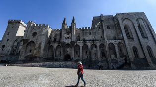 Une passante devant le Palais des papes d'Avignon, haut lieu du Festival international de théâtre d'Avignon, en 2019. (BORIS HORVAT / AFP)