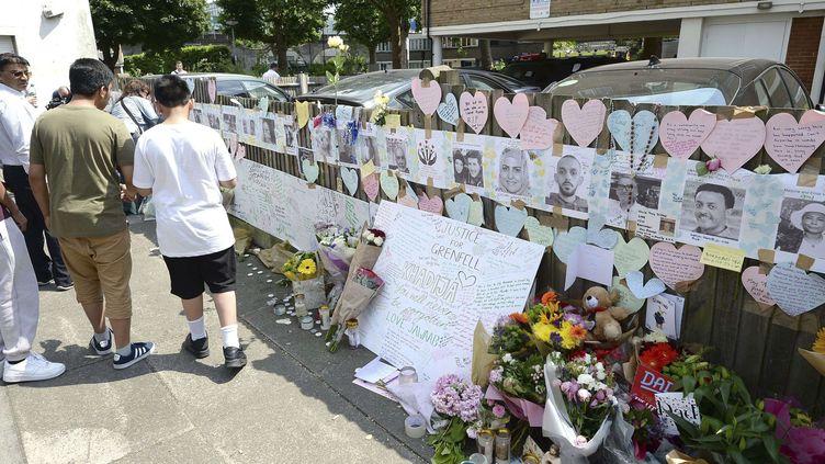 Des Londoniens ont déposé des fleurs devant des portraits de personnes disparues dans l'incendie de la tour Grenfell, dans le quartier de North Kensington, dimanche 18 juin 2017. (JOHN STILLWELL / SIPA / AP)