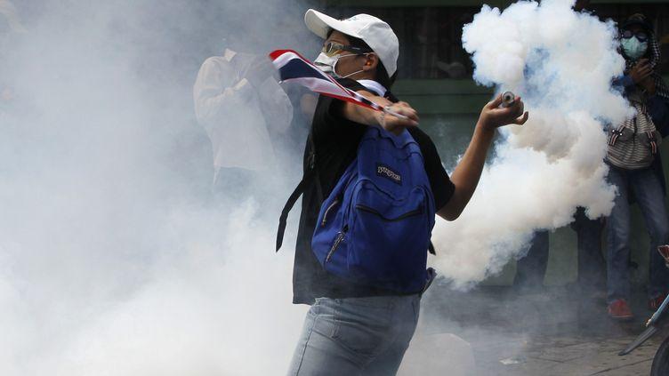 Un manifestant antigouvernemental envoie des gaz sur les forces de l'ordre, le 1er décembre 2013 à Bangkok (Thaïlande). (CHAIWAT SUBPRASOM / REUTERS)