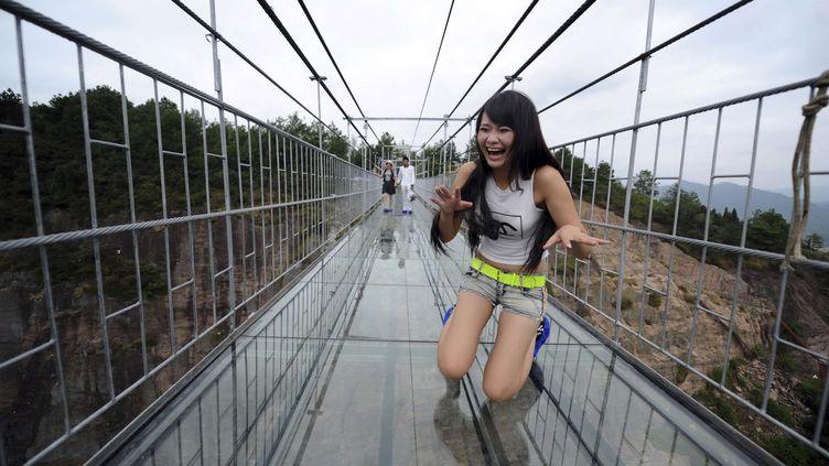Une touriste chinoise sur le pont qui traverse le pont de verreinauguré dans le parc géologique de Shiniuzhai, dans le comté de Pingjiang, le 24 septembre 2015. (AP/SIPA / AP)