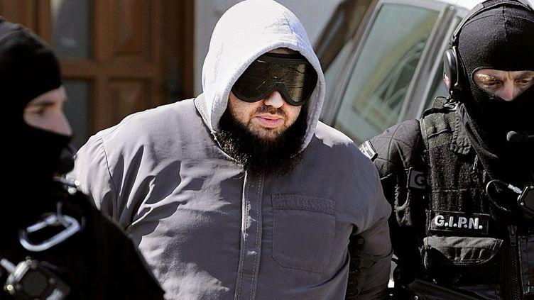 Le groupe d'intervention de la police nationale (GIPN) emmène Mohamed Achamlane, arrêté le 30 mars 2012 à son domicile de Bouguenais, près de Nantes (Loire-Atlantique). (JEAN-SEBASTIEN EVRARD / AFP)