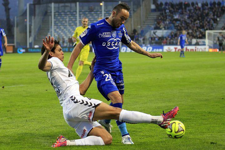 Le milieu de terrain bastiais Gaël Danic (à droite) est stoppé par le défenseur rémois Aissa Mendi, lors du match Bastia-Reims, le 18 avril 2015. (PASCAL POCHARD CASABIANCA / AFP)