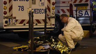 Un médecin du Samu prend en charge une personne blessée au Bataclan lors des attentats du 13-Novembre 2015 (DOMINIQUE FAGET / AFP)