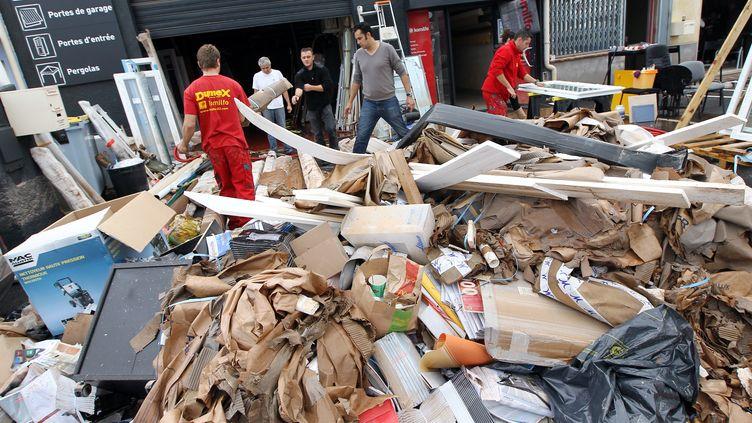 Des ouvriers nettoient une zone industrielle touchée par les inondations, à Fréjus (Var), le 8 novembre 2011. (VALERY HACHE / AFP)