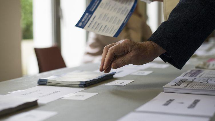 Un électeur prend des listes de candidats pour les élections européennes dans un bureau de vote à Saint-Cloud (Hauts-de-Seine), le 25 mai 2014. (FRED DUFOUR / AFP)
