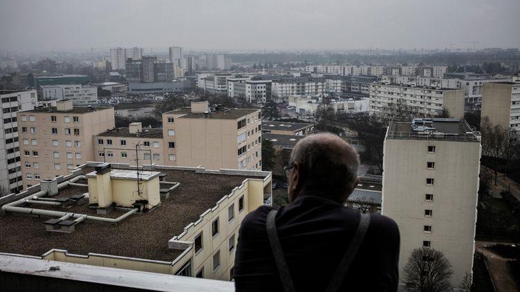 Un habitant de Vaulx-en-Velin regardepar sa fenêtre les grands ensembles de la commune de la banlieue est de Lyon (Rhône), en 2017. Photo d'illustration. (JEFF PACHOUD / AFP)
