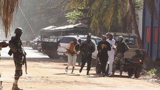 Des personnes s'éloignent en courant de l'hôtel Radisson, à Bamako, où se déroule une prise d'otages, le 20 novembre 2015. (HAROUNA TRAORE / AP / SIPA)