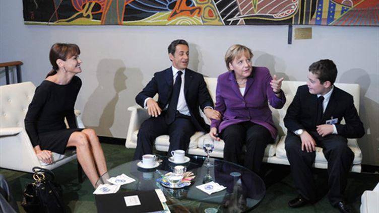 Nicolas Sarkozy et Angela Merkel, entourés de Carla Bruni-Sarkozy et du fils cadet de Nicolas Sarkozy, Louis. (AFP - Mehdi Taamallah)