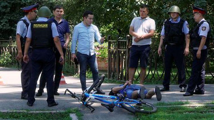 Les passants et les forces de l'ordre entourent l'un des tireurs présumés de la fusillade à Almaty. (Shamil Zhumatov)