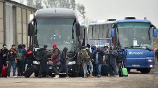 """Après être passés dans un bâtiment servant de """"gare routière"""", des migrants quittent la """"jungle"""" de Calais lundi 24 octobre (PHILIPPE HUGUEN / AFP)"""