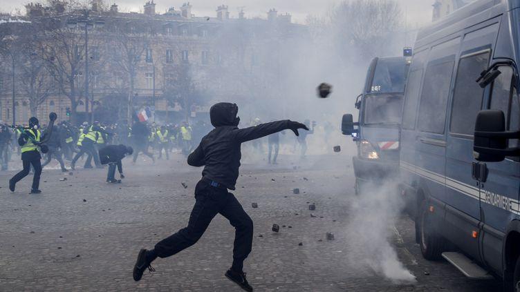 Une casseur lance des pavés sur les véhicules de la gendarmerie positionnés sur la place de l'Etoile à Paris, samedi 16 mars 2019. (GEOFFROY VAN DER HASSELT / AFP)