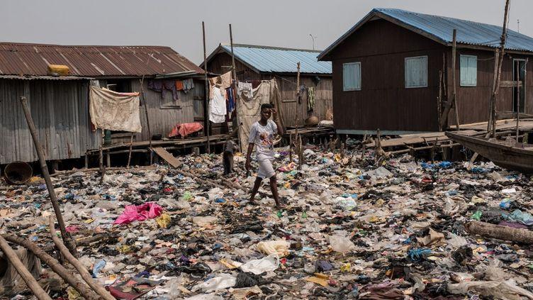 Une jeune femme marche dans les immondices dans un village informel de la lagune de Lagos. Cliché pris le 22 janvier 2019. (FLORIAN PLAUCHEUR / AFP)