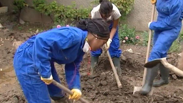 Des adolescents toulousains aident aux opérations de remise en état du village de Lassur (Ariège), après une coulée de boue, début août 2014. ( FRANCE 3 / FRANCETV INFO)